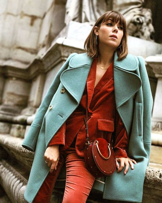 a rust velvet pantsuit, a mint-colored coat and a rust leather and suede crossbody