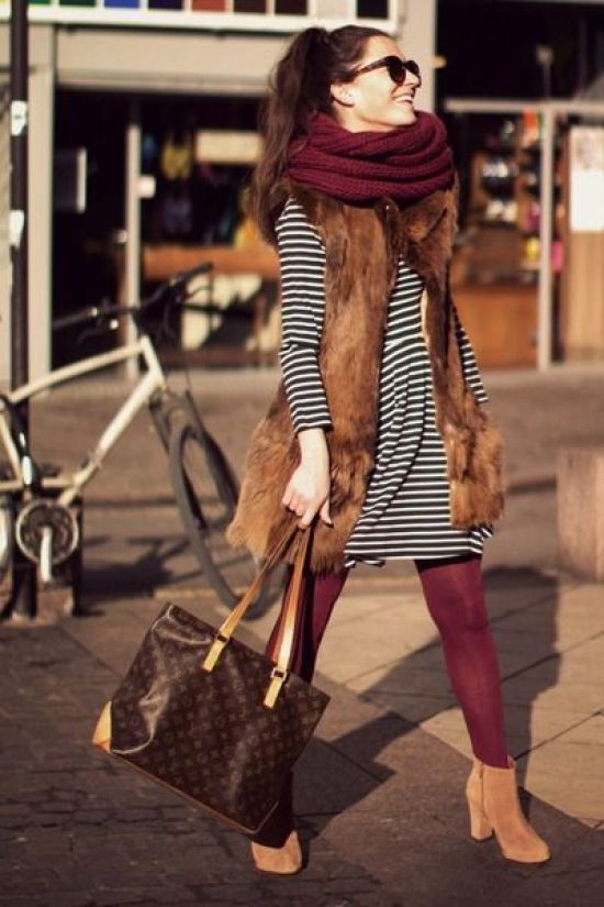 a striped short dress, burgundy tights, amber boots, a faux fur waistcoat, a burgundy scarf and a bag