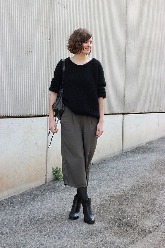 grey culottes, a black cashmere sweater, grey tights, black booties and a black bag