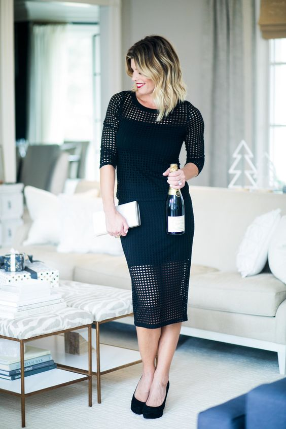 a black dress with a short uderdress and a net piece over it with long sleeves and black heels