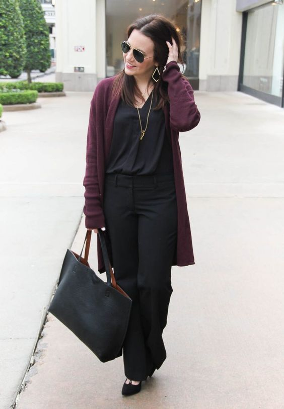 a black top, pants, shoes and a bag plus a plum-colored long cardigan for warmth