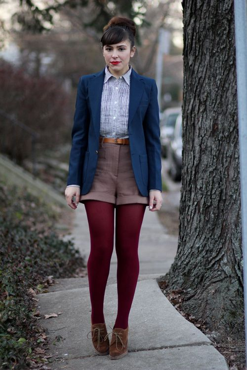 a blue shirt, brown shorts, a navy blazer, burgundy tights and suede brown shoes