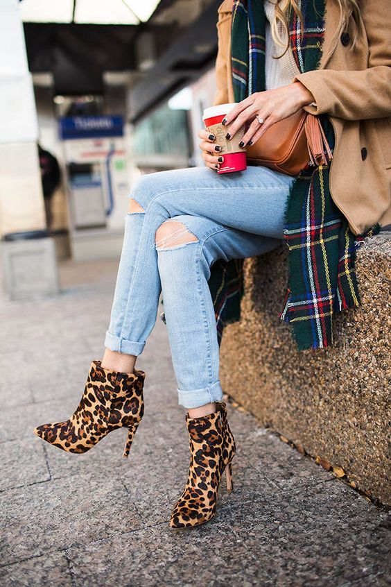 a chic look with a white sweater, blue ripped jeans, a plaid scarf, a camel coat and leopard print boots