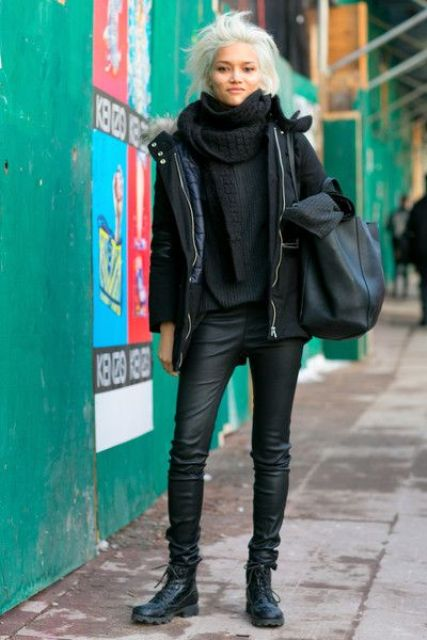 a total black look with a sweater, a scarf, leather pants, a parka and combat boots