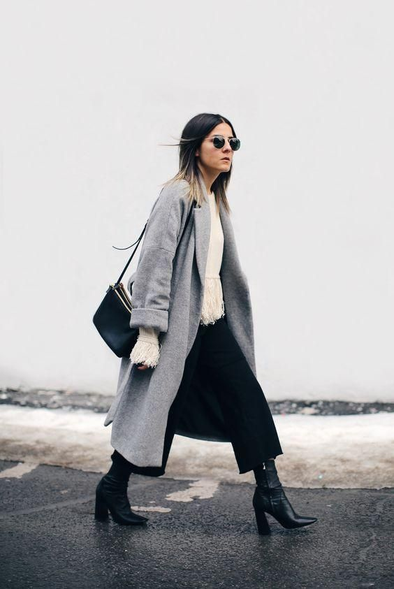 a white sweater with fringe, black culottes, a grey coat, black booties for a boho minimal look