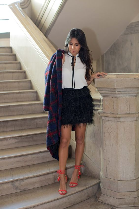 a white top with a bow, a black feather skirt, red lace up shoes and a plaid coat for holidays