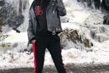 09 a black and red tracksuit, a black leather jacket and grey sock boots with pants tucked in