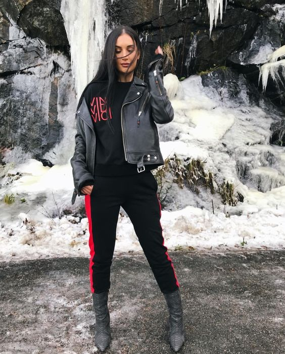 a black and red tracksuit, a black leather jacket and grey sock boots with pants tucked in