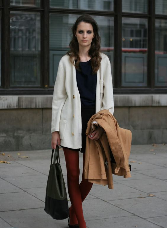 a black dress, a creamy cardigan, a camel coat, rust-colored tights, black flats