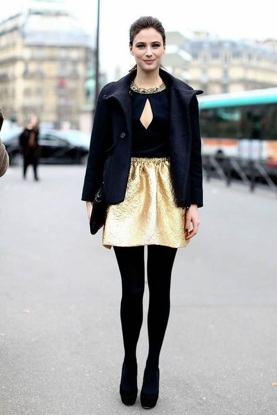 a black top with an embellished neckline, a gold mini, black tights and shoes plus a short coat