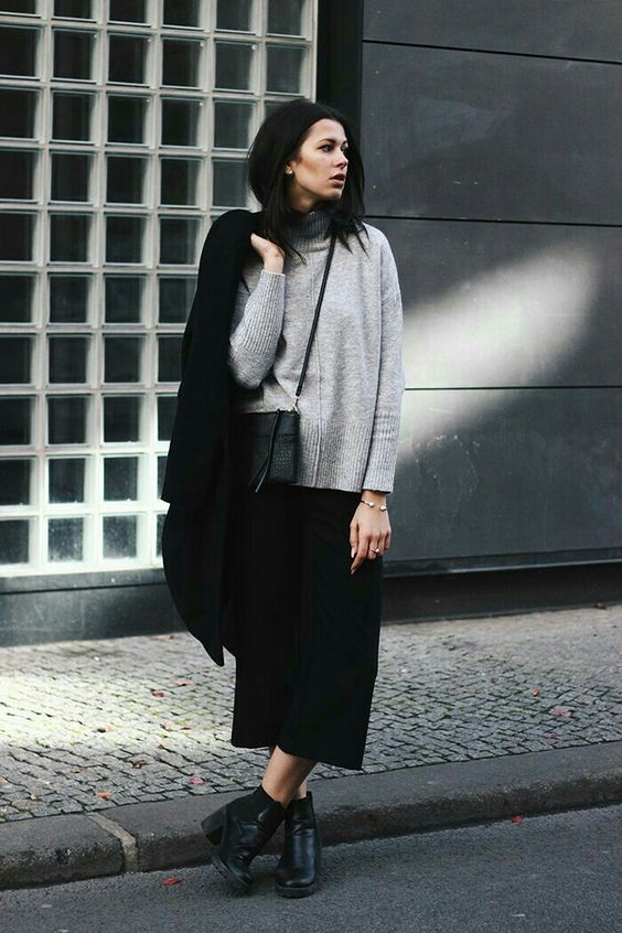 a grey sweater, black culottes, black booties, a black coat and a bag for a minimalist look