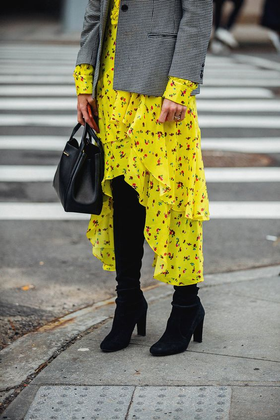 a neon yellow ruffled floral high low dress, a plaid short coat, black boots and a black bag
