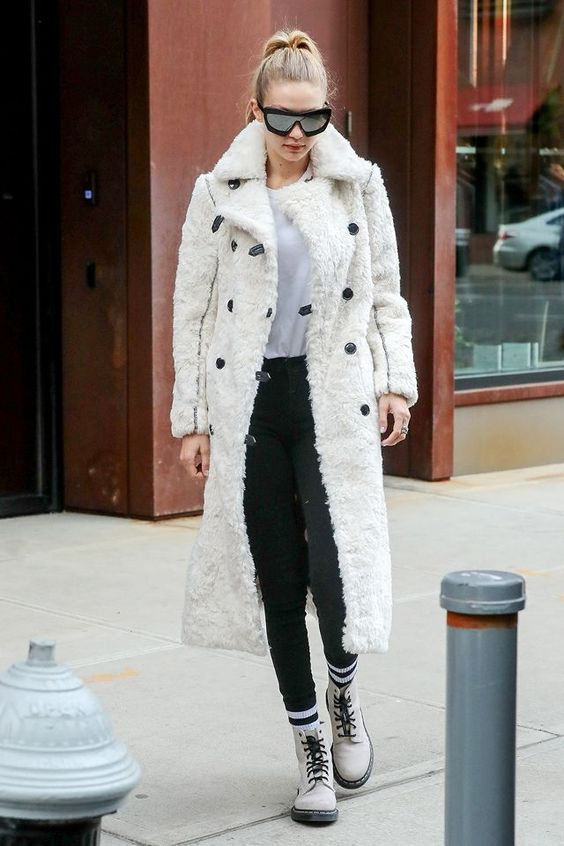 a white tee, black jeans, creamy combat boots and a matching faux fur coat by Gigi Hadid