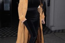 10 a black velvet tracksuit, metallic sock boots and a camel coat by Kim Kardashian