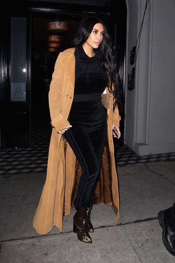 a black velvet tracksuit, metallic sock boots and a camel coat by Kim Kardashian