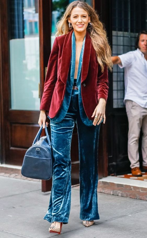 a blue velvet pantsuit, a burgundy velvet blazer on top and a blue bag for a layered look
