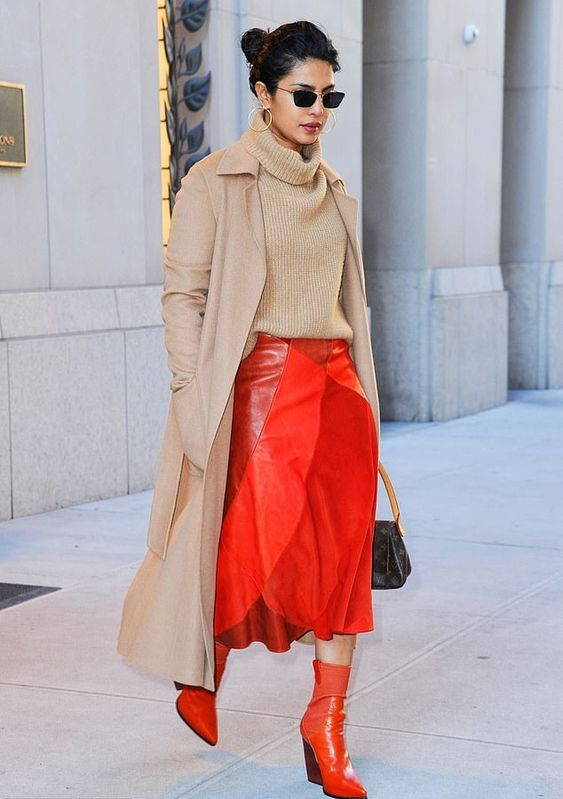 a camel coat and turtleneck, a red leather midi skirt, red boots and a brown bag