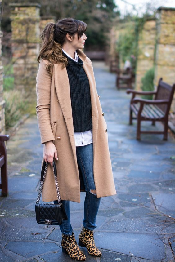 a comfy layered look with a shirt, a sweater, blue ripped jeans, a camel coat and leopard print boots