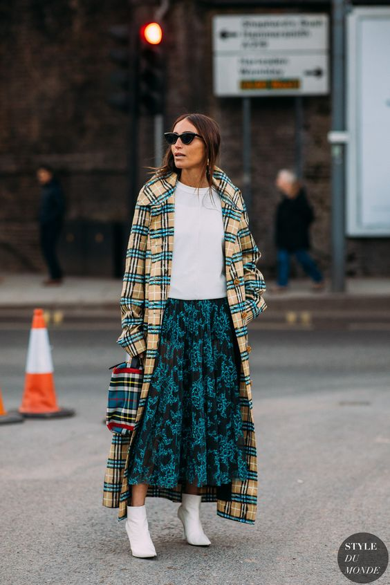 a white sweatshirt, a teal midi floral skirt, a plaid coat, white booties and a plaid bag