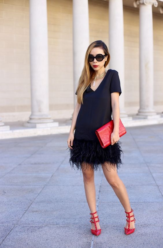 a black dress with a feather skirt, a red clutch and red spike shoes plus a statement necklace