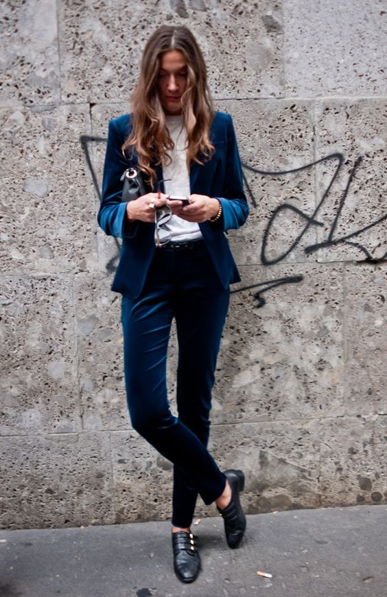 a bold blue velvet pantsuit, black flat shoes and a white top for a chic and refined look