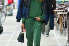11 a grass green tracksuit, black sock boots, a puff coat with a color block effect