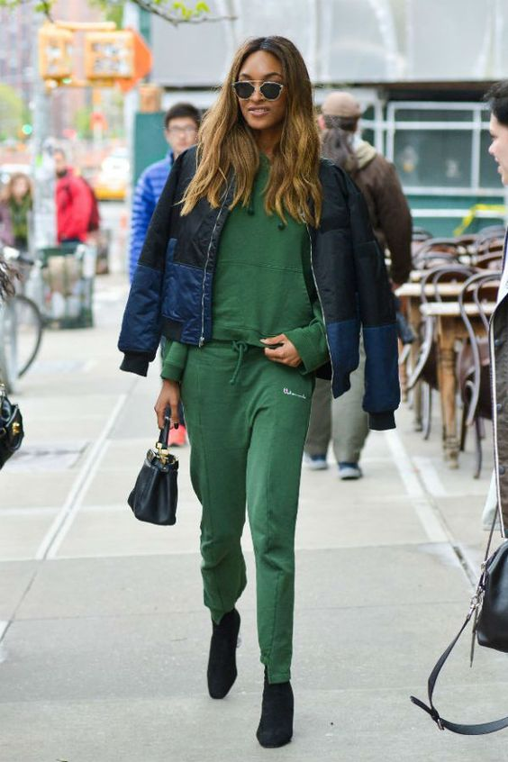a grass green tracksuit, black sock boots, a puff coat with a color block effect