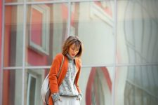 11 a grey A-line midi skirt, a grey sweater, mustard tall boots, an orange coat to add color