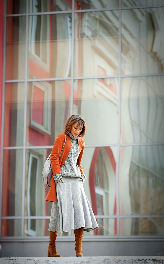 a grey A-line midi skirt, a grey sweater, mustard tall boots, an orange coat to add color