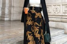 11 a white turtleneck, a moody floral A-line midi skirt, black boots, a black coat, a beret and a forest green bag