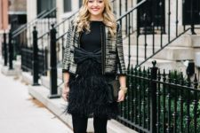 12 a black dress with a large bow and a feather skirt, black tights, embellished shoes and a gild blazer