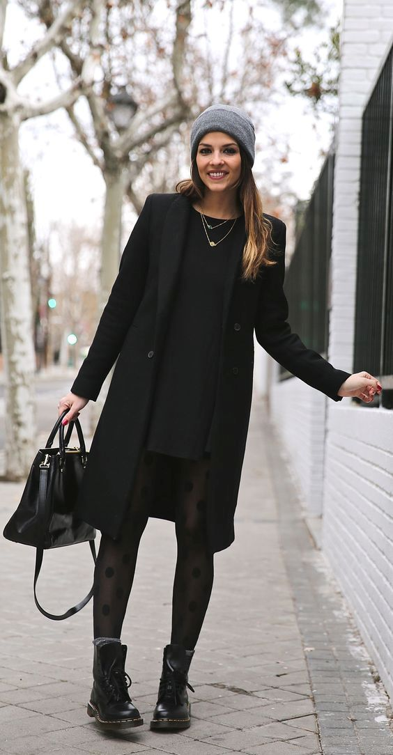 a black mini dress, a black coat, black printed tights, black boots, a black bag and a grey beanie
