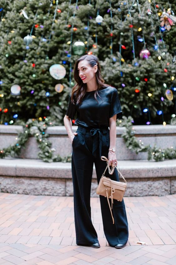 a black silk jumpsuit with wideleg pants, heels and a bow on the waist and a neutral bag