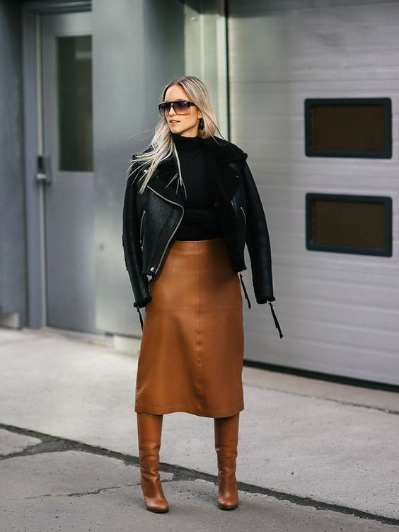 a black turtleneck, a black shearling coat and a camel leather skirt and boots