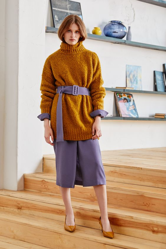a mustard oversized sweater over a purple dress with long sleeves and mustard heels