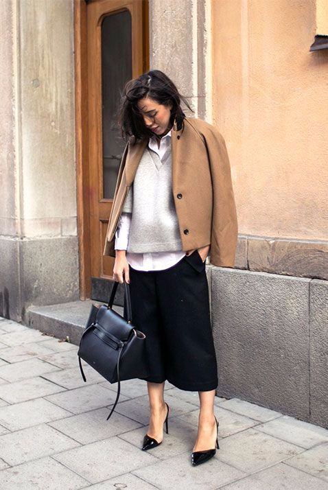 a white shirt, a grey V neck sweater, black culottes, black shoes, a camel short coat and a black bag