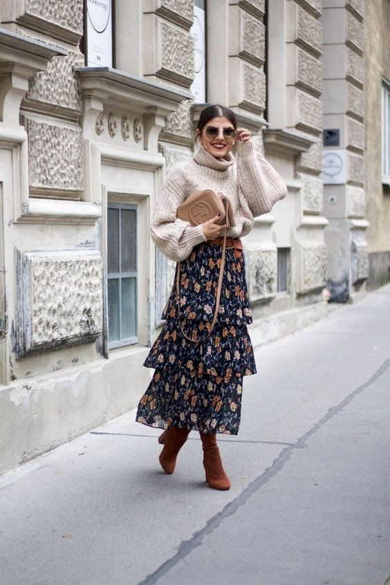 an oversized neutral sweater, a floral layered midi skirt, cognac boots and a neutrla bag