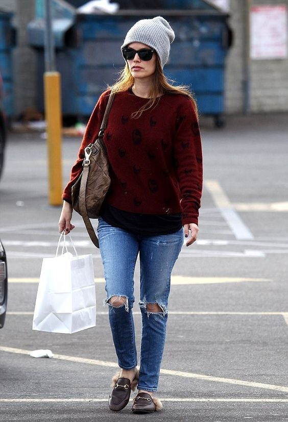 a bold burgundy sweater, rippped blue jeans, faux fur loafers and a beanie