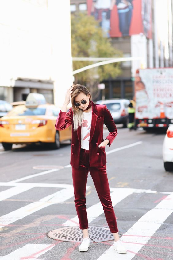 a burgundy velvet suit with cropped pants, a printed tee, a choker and white sneakers for a bold statement