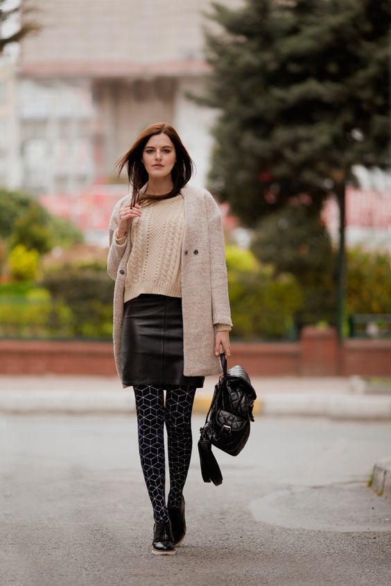 a creamy sweater, a black leather mini, an off-white cardigan, printed tights, black shoes and a backpack