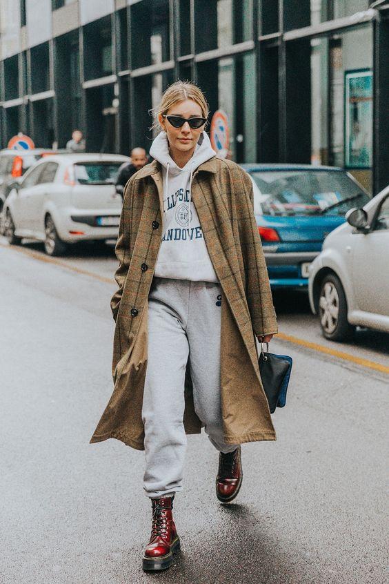 a grey tracksuit, a windowpane camel coat, burgundy combat boots