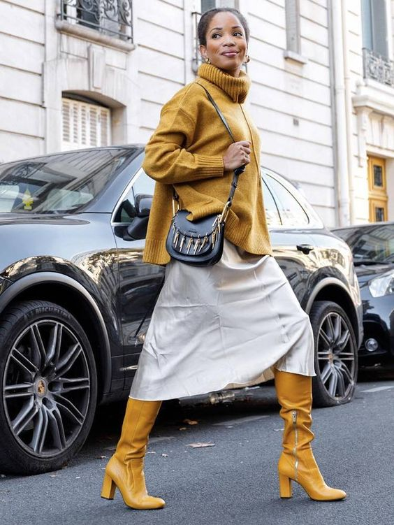 a neutral midi skirt, a mustard turtleneck oversized sweater, yellow tall boots and a black bag