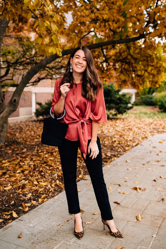 a red silk blouse, black pants, a black velvet bucket bag and leopard print shoes