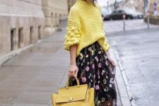 13 black lacquer boots, a floral A-line midi skirt, a neon yellow oversized sweater and a mathcing bag
