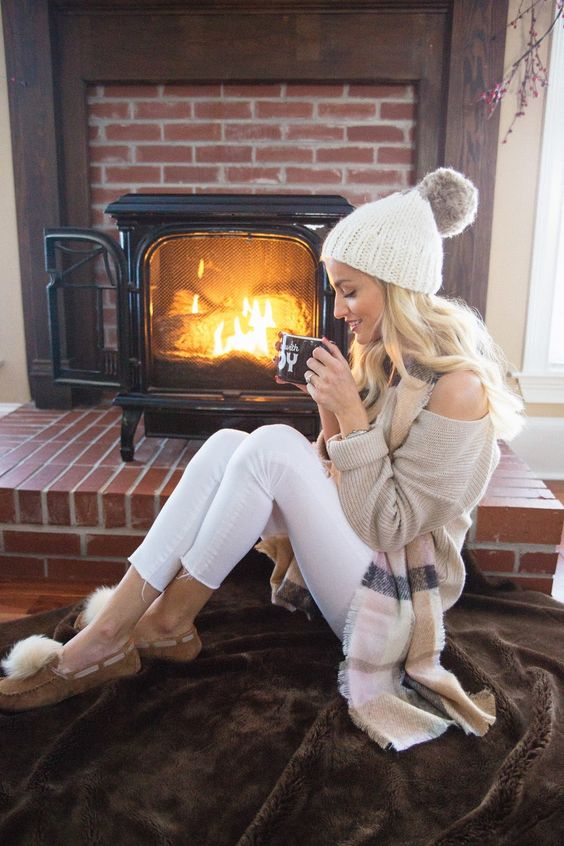 white leggings, a neutral one shoulder sweater, moccasins with fur and a knit beanie