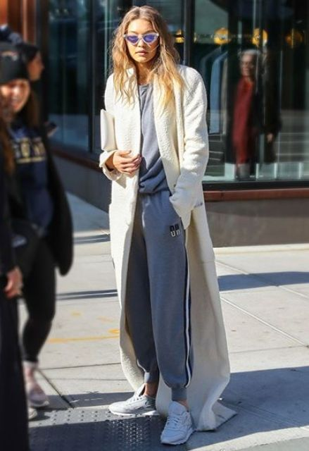 a grey tracksuit, white trainers and a long creamy duster coat by Gigi Hadid