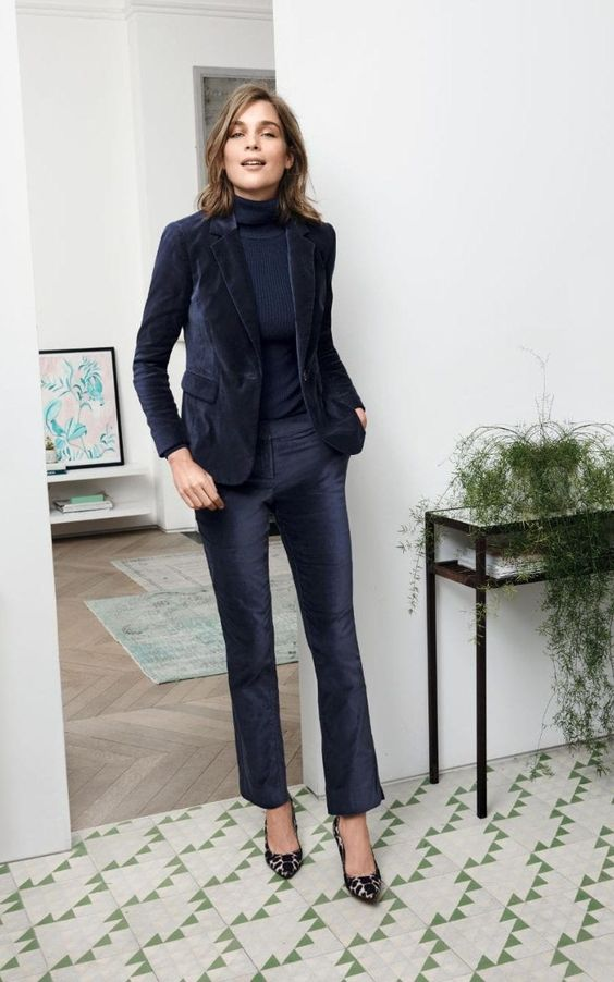 a navy velvet pantsuit with a matching turtleneck and printed shoes for a retro inspired work look
