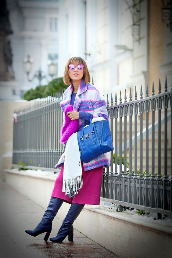 a purple top, a pink midi skirt, navy tall boots, a colorful plaid coat and a hot pink beanie