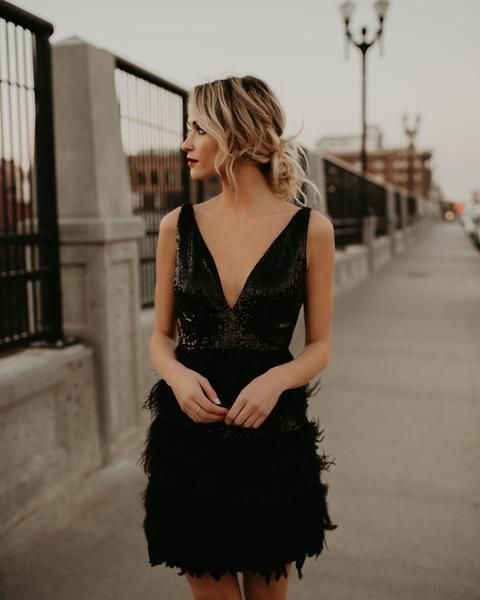 a statement dress with a sequin bodice and a feather skirt and a plunging neckline is all you need to strike
