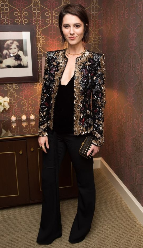 black pants, a black velvet top, a heavily embellished blazer and an embellished clutch for a shiny look